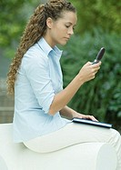 Young woman sitting on arm of chair, checking cell phone messages