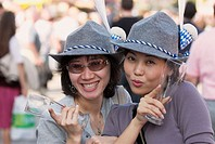 Two Japanese girls with traditional Bavarian costume at Oktoberfest. Munich, Bavaria, Germany