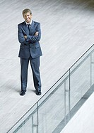 Businessman standing with arms folded, high angle view