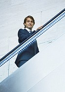 Businessman going up on escalator