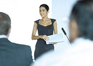 Executive woman standing next to microphone during seminar