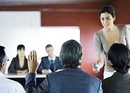 Executives sitting in seminar, woman holding microphone to man raising hand