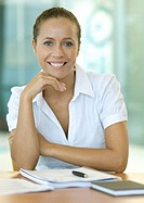 Businesswoman sitting at desk, smiling at camera, portrait