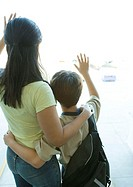 Mother and boy looking out airport window, waving