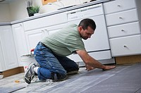 Construction worker laying tile