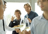 Two male executives raising glasses of champagne during office party (thumbnail)