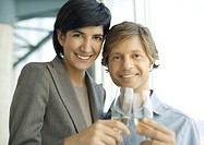 Professional man and woman clinking glasses of champagne, smiling at camera