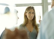 Young woman holding up glass of champagne during office party