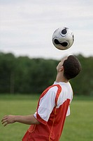 Side profile of a soccer player heading a ball