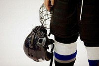 Mid section view of an ice hockey player holding a helmet