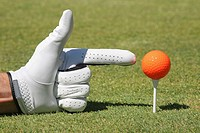 Close-up of a person´s hand pointing at a golf ball on a golf tee