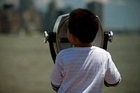 Rear view of a boy looking through coin-operated binoculars, Manhattan, New York City, New York State, USA