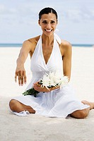 Portrait of a young woman sitting on the beach and smiling