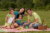 Parents and their two daughters sitting on a picnic blanket