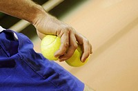 Close-up of a person's hand holding two tennis balls