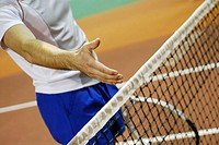Close-up of a person's hand over a tennis net