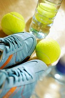 Close-up of two tennis balls with a pair of tennis shoe and a water bottle