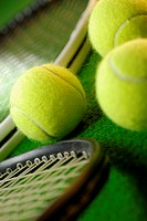 Close-up of three tennis balls and two tennis rackets