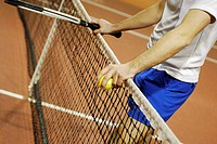 Mid section view of a man leaning against a tennis net