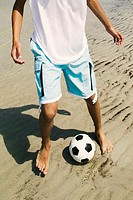 Low section view of a person playing with a soccer ball on the beach