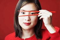 Portrait of a young woman holding chopsticks in front of her face