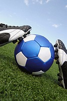 Close-up of soccer shoes and a soccer ball