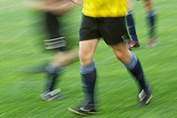 Low section view of two soccer players and a referee