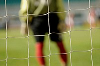 Mid section view of a goalie standing at the goal post