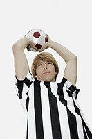Low angle view of a soccer player holding a soccer ball over his head