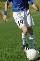 Low section view of a soccer player running with a soccer ball