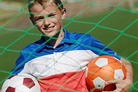 Portrait of a soccer player standing behind the net and holding two soccer balls