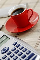 Close-up of a calculator and a cup of black tea