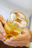 Close-up of a person's hands holding a glass of lemonade with ice cubes (thumbnail)