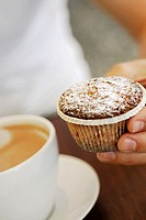 Close-up of a person´s hand holding a cupcake