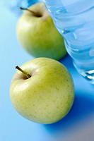 Close-up of two apples and a water bottle