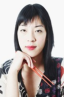 Portrait of a young woman holding chopsticks