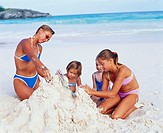 Close-up of a mid adult woman with her three daughters making a castle on the beach, Bermuda