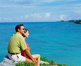 Side profile of a young couple sitting together on a rock, Bermuda