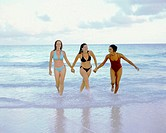 Three young women walking and holding hands on the beach, Bermuda