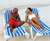 Young couple lying on lounge chairs and looking at each other, Bermuda (thumbnail)