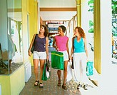 Three young women walking on a walkway and holding shopping bags, Bermuda