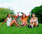 Portrait of three young women sitting on the grass in front of bicycles, Bermuda