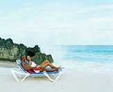 Side profile of a young couple lying on lounge chairs on the beach, Bermuda