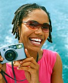 Portrait of a young woman holding a digital camera and smiling, Bermuda