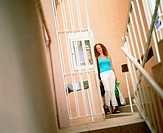 Young woman holding shopping bags and standing on a staircase, Bermuda
