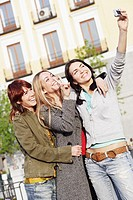 Young woman taking a photograph of herself with her two friends