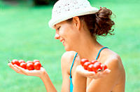 Woman holding handfuls of tomatoes