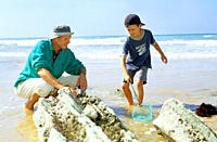Father and son with net at beach