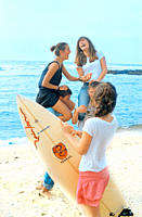 Young girl holding surfboard next to teenagers at beach