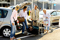 Senior couple and young couple putting luggage in car